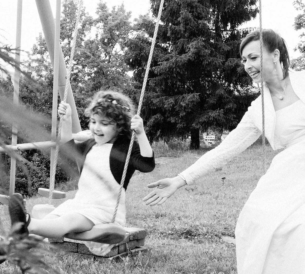 La sposa gioca con la sua bambina sull'altalena prima del matrimonio