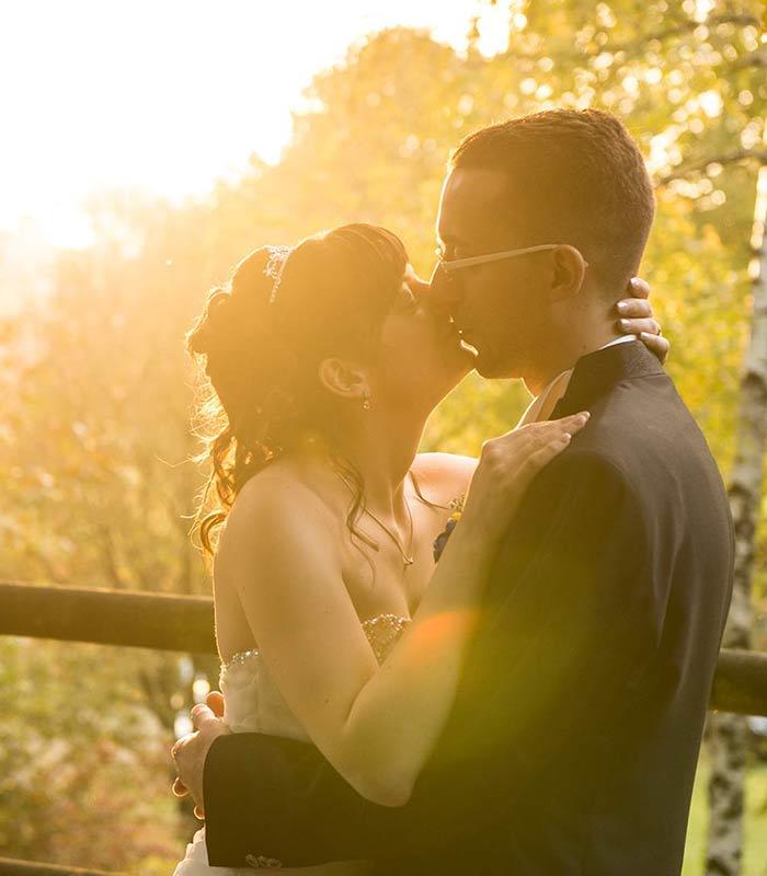 Gli sposi si baciano illuminati dal caldo sole del pomeriggio